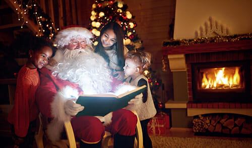 Father Christmas sits with book and children by fireplace